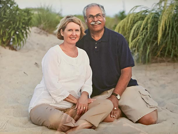 a woman and a man sit in the sand on a beach