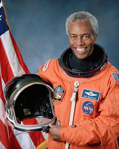 Guion Bluford, wearing a NASA spacesuit, holding a helmet, poses with an american flag