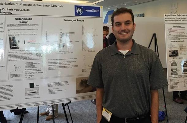 a man stands in front of a research poster
