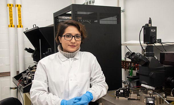 A woman in a white lab coat, blue gloves, and glasses sits next to a microscope in a lab and smiles