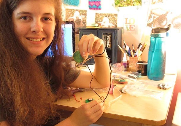 A girl smiles at the camera while holding up a green circular object that is attached to wires.