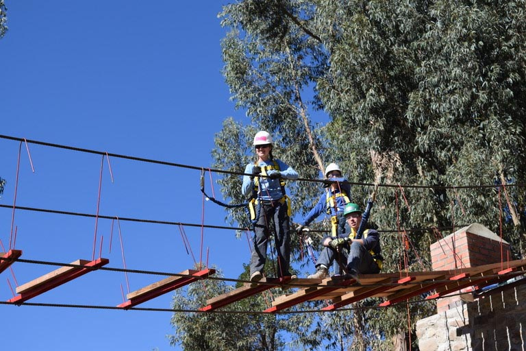 Three students wearing personal protective equipment stand on a partially constructed pedestrian bridge.