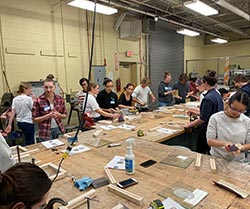 A group of people stand around a large table covered in making materials and power tools.