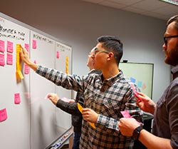 Three men place sticky notes on a whiteboard.