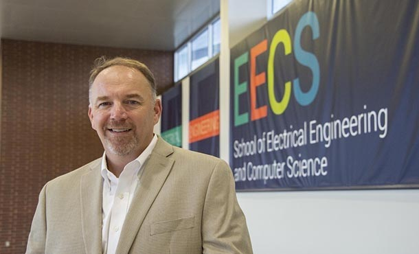 A man stands in front of a banner that reads E E C S