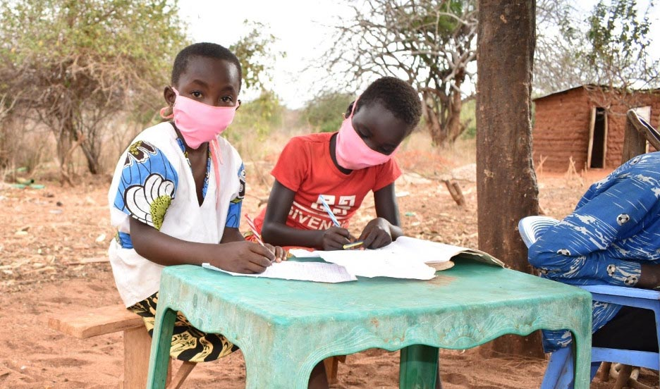 two children wearing face masks sit at a table outside working on a literacy boot camp assignment
