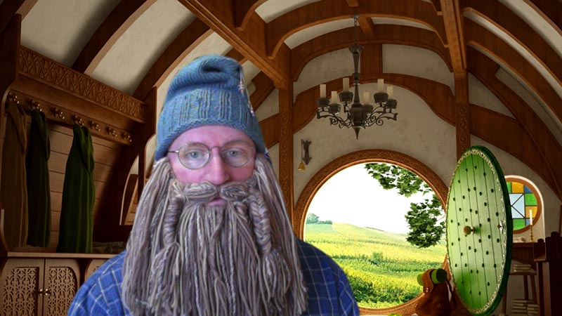 man dressed as Gandalf from The Hobbit movie standing in front of Hobbit-themed virtual background