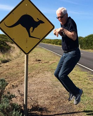 a man standing next to a kangaroo crossing road sign jumps in the air, mimicking a kangaroo