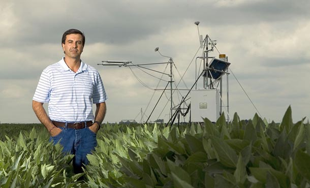 a man stands in an agricultural field with monitoring equipment in the background