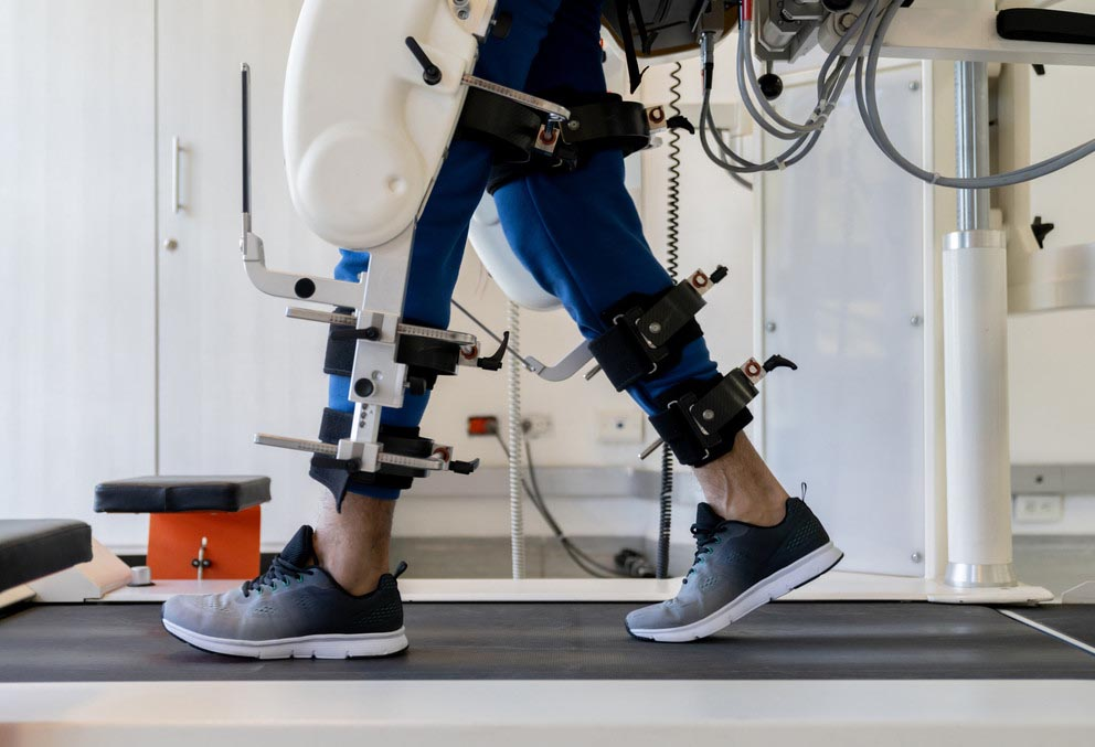 a person walks on a treadmill with a robotic exoskeleton attached to their leg