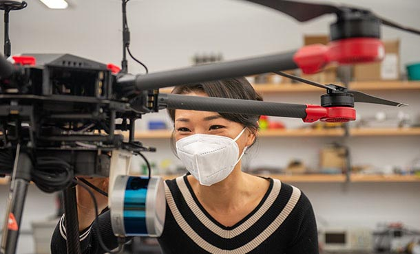 A woman in a black sweater and a white face mask adjusts a black drone.