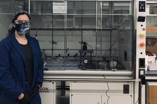 a student in lab attire poses next to a fume hood in an engineering lab